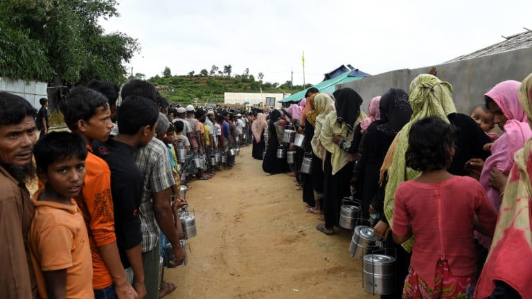 Rohingya refugees queue for a meal provided by an aid agency in Bangladesh.