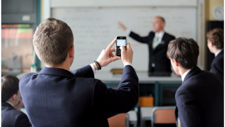 A new review of the evidence on the impact of phones in classrooms has found that schools have taken opposing stances.