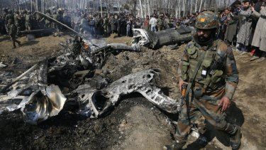 An Indian soldier walks past the wreckage of an Indian aircraft after it crashed in the outskirts of Indian controlled Kashmir.