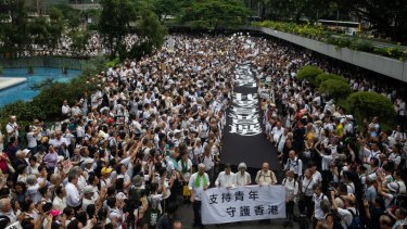 Demonstrators carry  banners during a protest organised by the elderly in the central district of Hong Kong on July 17.