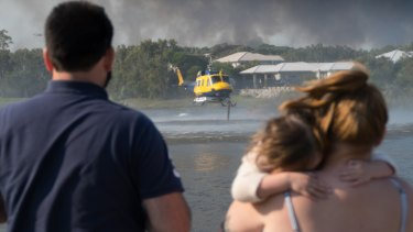A helicopter taking on water at Peregian Spring Golf Course to water-bomb the Sunshine Coast bushfires on Tuesday.