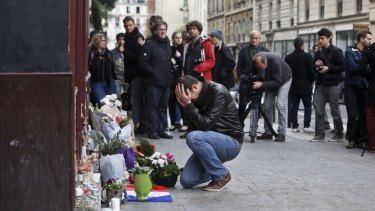A man holds his head in his hands as he lays flowers in front of the Carillon cafe in Paris after the 2015 terror attacks. Then French president Francois Hollande vowed to attack Islamic State without mercy.