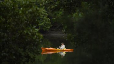 A man fishing from his small boat on the Cooks River at Kendrick Park.