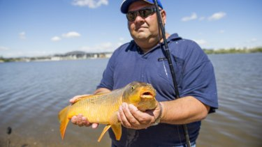 Charlie Diedo catches carp on the shore of Lake Burley Griffin in Canberra.
