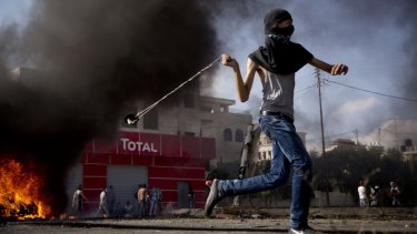 A young Palestinian hurls a stone during clashes with Israeli troops near Ramallah.