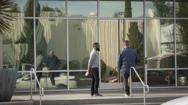 People stand outside an Apple satellite office building in Sunnyvale, California.