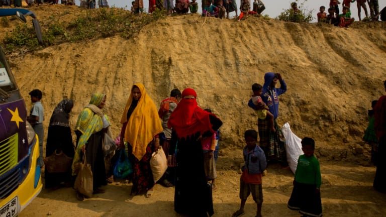 Rohingya Muslims watch from atop a hill as new refugees arrive in Balukhali refugee camp, Bangladesh.