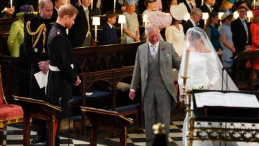 Britain's Prince Harry looks at Meghan Markle as she arrives accompanied by the Prince Charles during the wedding ceremony.