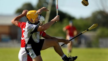 Sydney Shamrocks hurler and captain Niall Holmes (left) mid air as his hurley is snapped in half during a match against Central Coast at Ingleburn in May 2015.