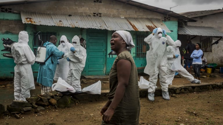 A relative grieves as a Red Cross burial team prepares to remove the body of an Ebola victim in central Monrovia, Liberia.