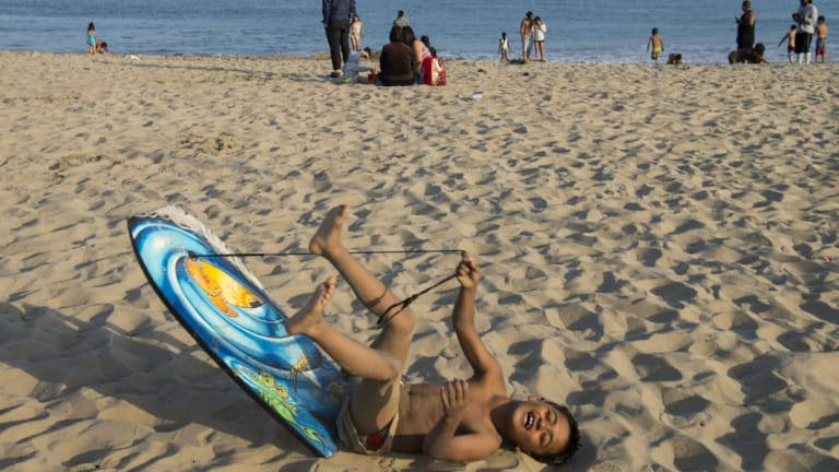 Thousands of Memorial Day beachgoers, including Gabriel Cordromp, 8, were ordered out of the water at Corona del Mar beach as authorities searched for the shark that attacked Korcsmaros the day before.