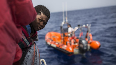 A child rescued from a rubber dinghy off the Libyan coast peers out from aboard the Open Arms aid boat.