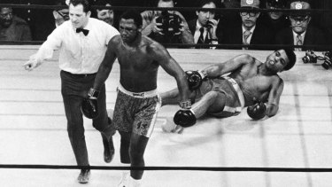 Boxer Joe Frazier being directed to the ropes after knocking down Muhammad Ali during the 15th round of the title bout in Madison Square Garden in New York in 1971.