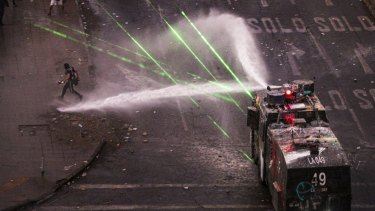 Police water cannon advances on anti-government demonstrators in Santiago, Chile, on Monday. Announced reforms have not yet satisfied protesters who want the President to resign.