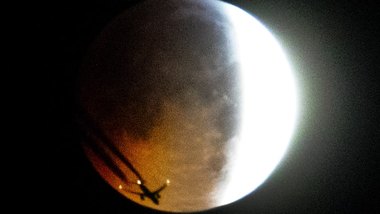 An aircraft flies across the face of the full moon as the lunar eclipse begins in Frankfurt early on Monday.