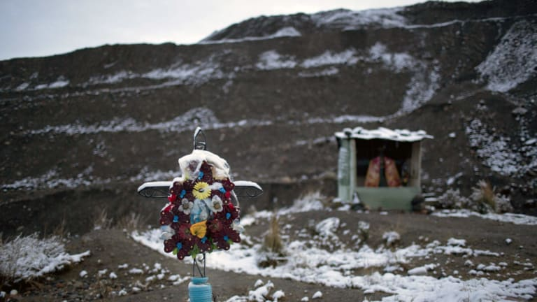 Dangerous work: Flowers adorn a tomb at an illegal gold mining camp in Ananea, in Peru's Puno region.
