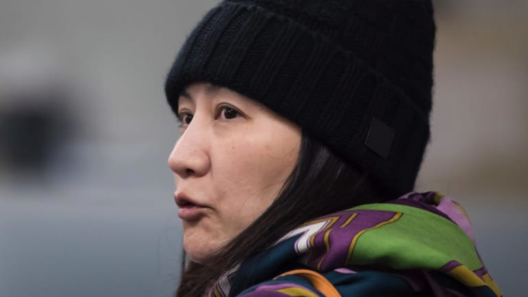 Huawei chief financial officer Meng Wanzhou talks with a member of her private security detail after they went into a wrong building while arriving at a parole office in Vancouver.