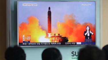 People watch a TV news channel airing an image of North Korea's ballistic missile launch in March last year.