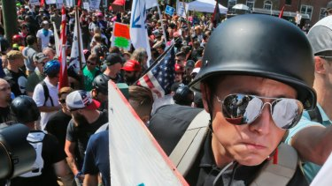 A white nationalist demonstrator with a helmet and shield walks into Lee Park in Charlottesville, Virginia in 2017.