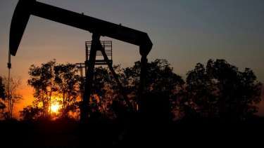 The sun sets behind an oil well in a field near El Tigre, Venezuela. The country exports oil to Russia as part payment for loans.