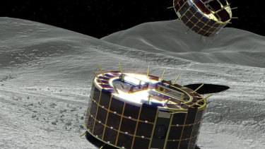 This computer graphic image shows two drum-shaped and solar-powered MINERVA-II 1 rovers on the asteroid.