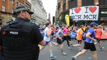 An armed police officer stands at the start of the Great Manchester Run in central Manchester after the bombing which killed 22 people.