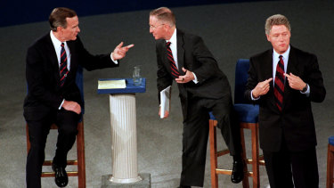 President George H.W. Bush, left, talks with independent candidate Ross Perot as Democratic candidate Bill Clinton stands aside at the end of their second presidential debate in 1992.