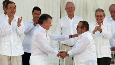 Colombian President Juan Manuel Santos, front left, and the top FARC commander, Rodrigo Londono, known by the alias Timochenko, shake hands after signing the 2016 peace agreement to end 50 years of conflict.