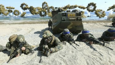 In this March 2016 photo, marines of the US, left, and South Korea, wearing blue headbands on their helmets, take positions after landing on a beach during the a joint military exercise.