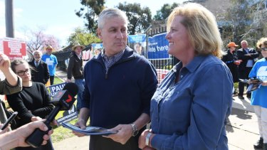Nationals leader Michael McCormack hands out how-to- vote cards with the Liberal's Julia Ham.