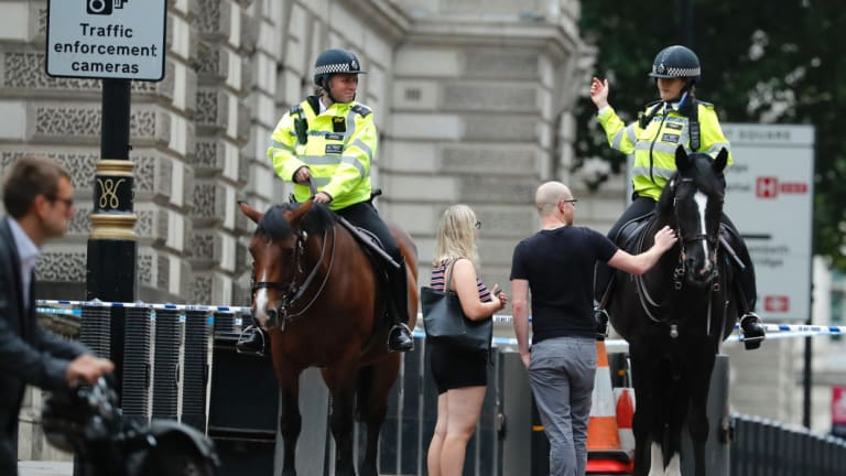 Mounted police officers block a road leading to the scene of the collision.