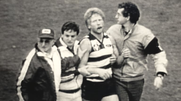 A distressed Neville Bruns is helped from the field in 1985.