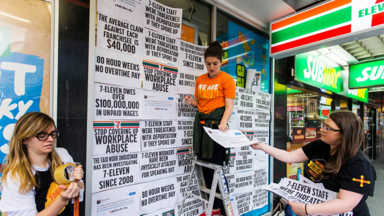 Protestors pin signs to the windows of a 7-Eleven store to protest about the company's worker exploitation and wage fraud scandal.