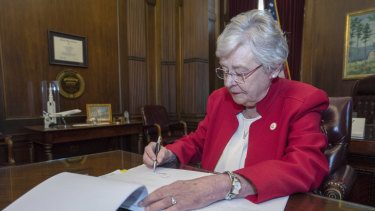 This photograph released by the state shows Alabama Governor Kay Ivey signing a bill that virtually outlaws abortion in the state on Wednesday.