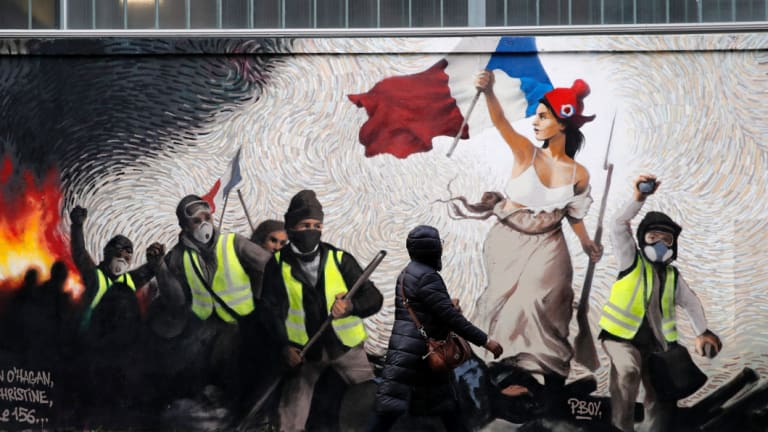 "A woman passes by a mural by street artist PBOY depicting Yellow Vest (gilets jaunes) protesters inspired by a painting by Eugene Delacroix, ""La Liberte guidant le Peuple""  in Paris on Thursday."