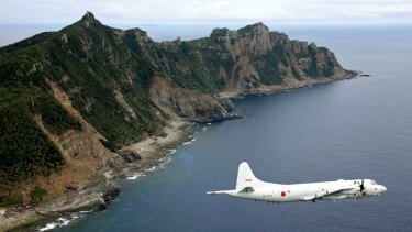 Japan Maritime Self-Defence Force P-3C Orion surveillance plane flies over the disputed islands, called the Senkaku in Japan and Diaoyu in China.