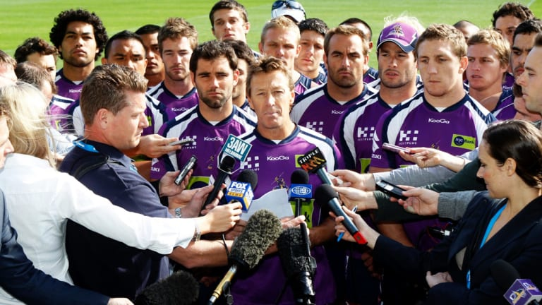 United front: Surrounded by all 22 players, Melbourne Storm coach Craig Bellamy addresses the media after the Storm were penalised for cheating the salary cap in 2010.