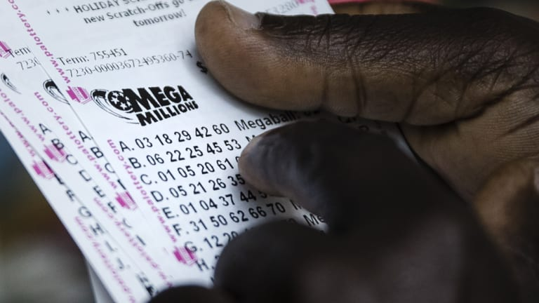 A lottery player looks over his Mega Millions lottery tickets he purchased at a news stand in Philadelphia.