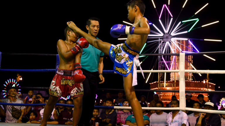 Mauy Thai fighter Samsun, 11, (left) is hit in the face with his opponent's foot during a bout.