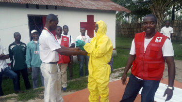 A Red Cross team dons protective clothing before heading out to look for suspected victims of Ebola, in Mbandaka.