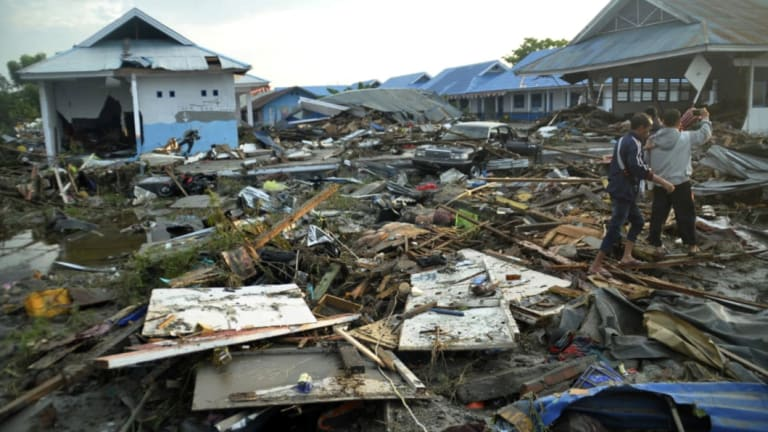 Indonesian men survey the damage following earthquakes and a tsunami in Palu, Central Sulawesi.