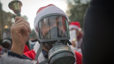 A Palestinian protester, dressed as Santa Claus with a teargas mask during a protest on Saturday.