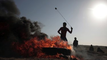 A Palestinian protester hurls stones toward Israeli soldiers during a protest near the Gaza Strip border with Israel on Saturday.