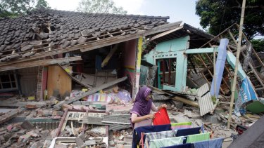 A woman dries her laundry in front of her home shortly after the quake in West Lombok.
