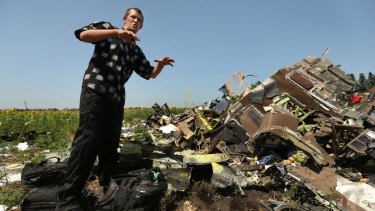 Donetsk People's Republic sniper Eugene Lukovkin, aged 30, stands among the pilots' bags at one of the sites where he witnessed the front section of Malaysian flight MH17 crashing.