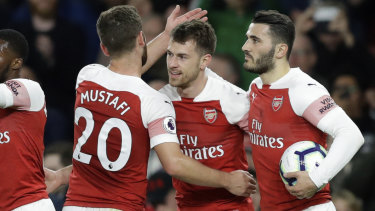 Celebrations: Arsenal teammates swamp Ramsey after he finally opened the scoring for Unai Emery's side.