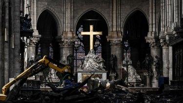 Rubble lies below the Pieta sculpture and a cross inside the Notre Dame de Paris cathedral.