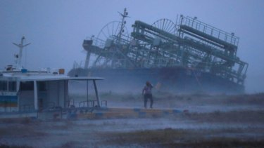 A vessel tilts after running ashore as typhoon Trami approached Yonabaru, southern Japan, on Saturday.