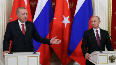 Turkey's President Recep Tayyip Erdogan, left, gestures as Russian President Vladimir Putin listens to him during a joint news conference following their talks in Moscow on Wednesday.