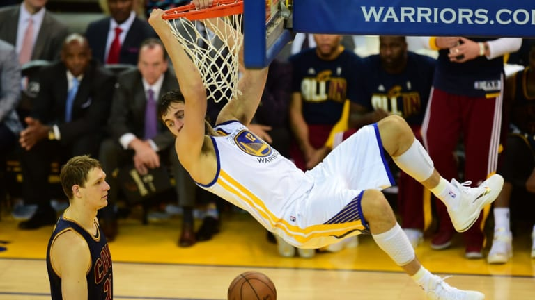 Hang time: Bogut clings to the rim after getting past Timofey Mozgov of the Cleveland Cavaliers.